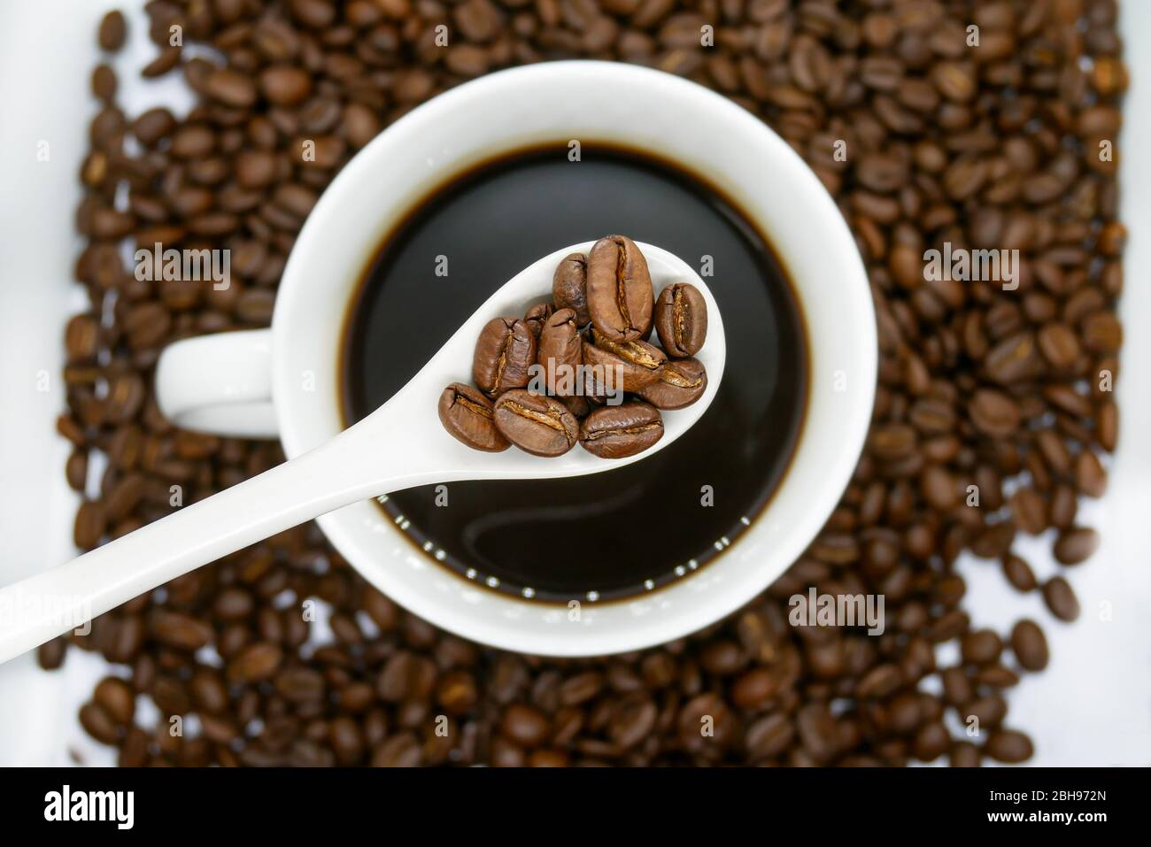 white coffee cup, spoon and roasted coffee beans that isolated on white background. top view. Stock Photo