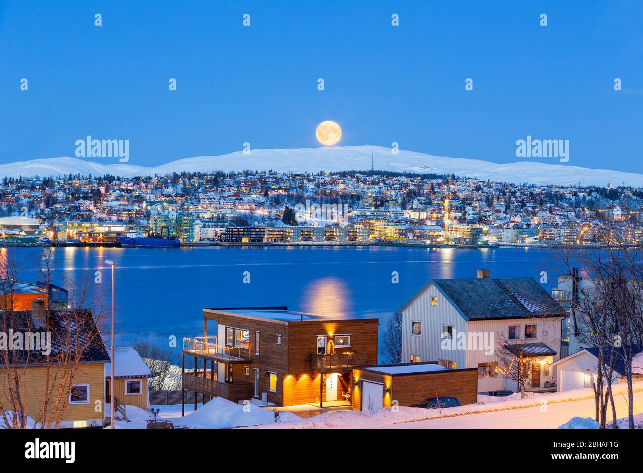 Tromso City At Full Moon In Winter Time, Christmas in Tromso, Norway Stock Photo