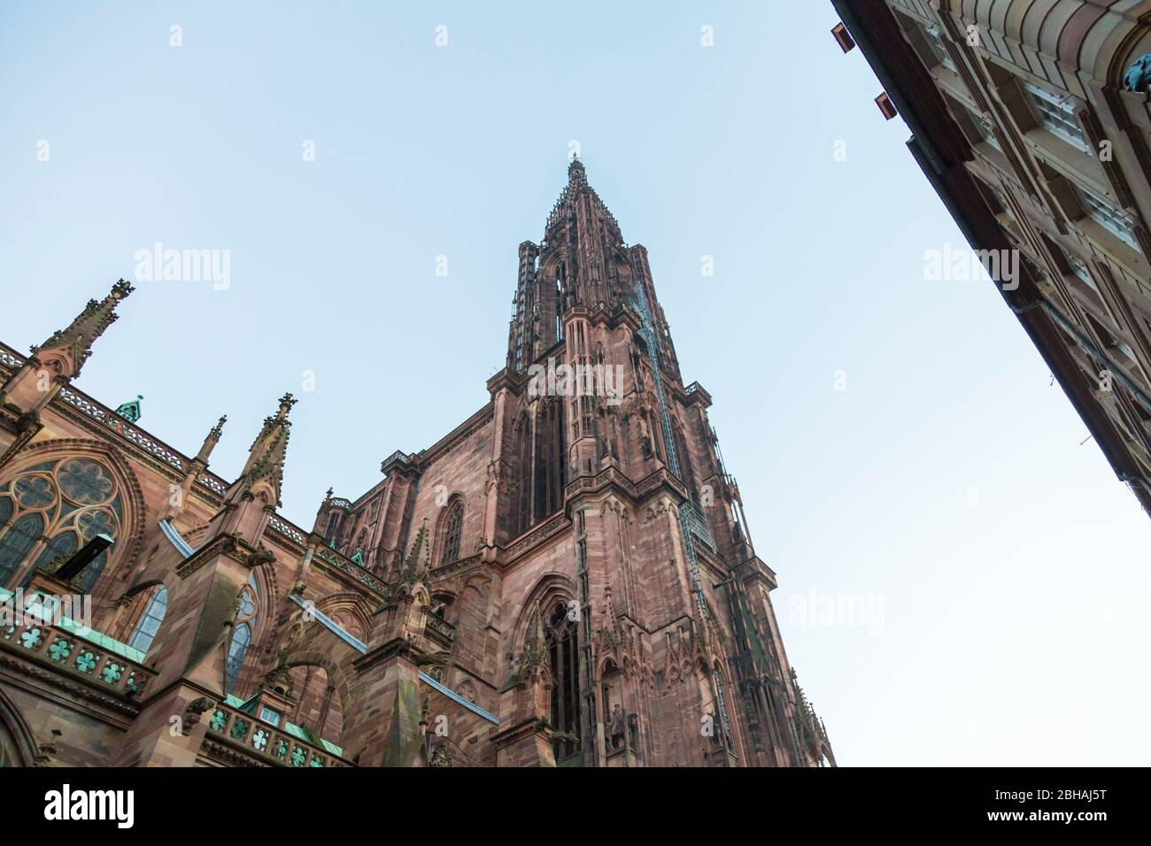 Ornate Gothic spire of Strasbourg Cathedral, Alsace, France viewed from below against a hazy sky Stock Photo