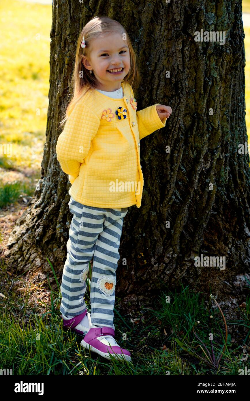 little girl leaning against the trunk of an old tree Stock Photo
