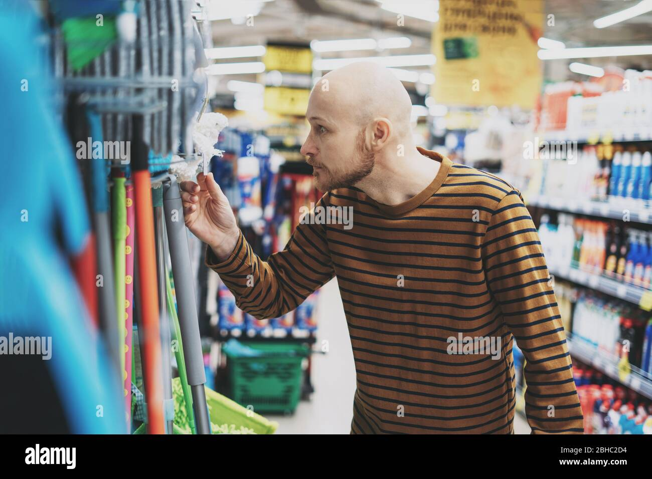 Adult bald bearded man shocked by price in hardware department of supermarket Stock Photo