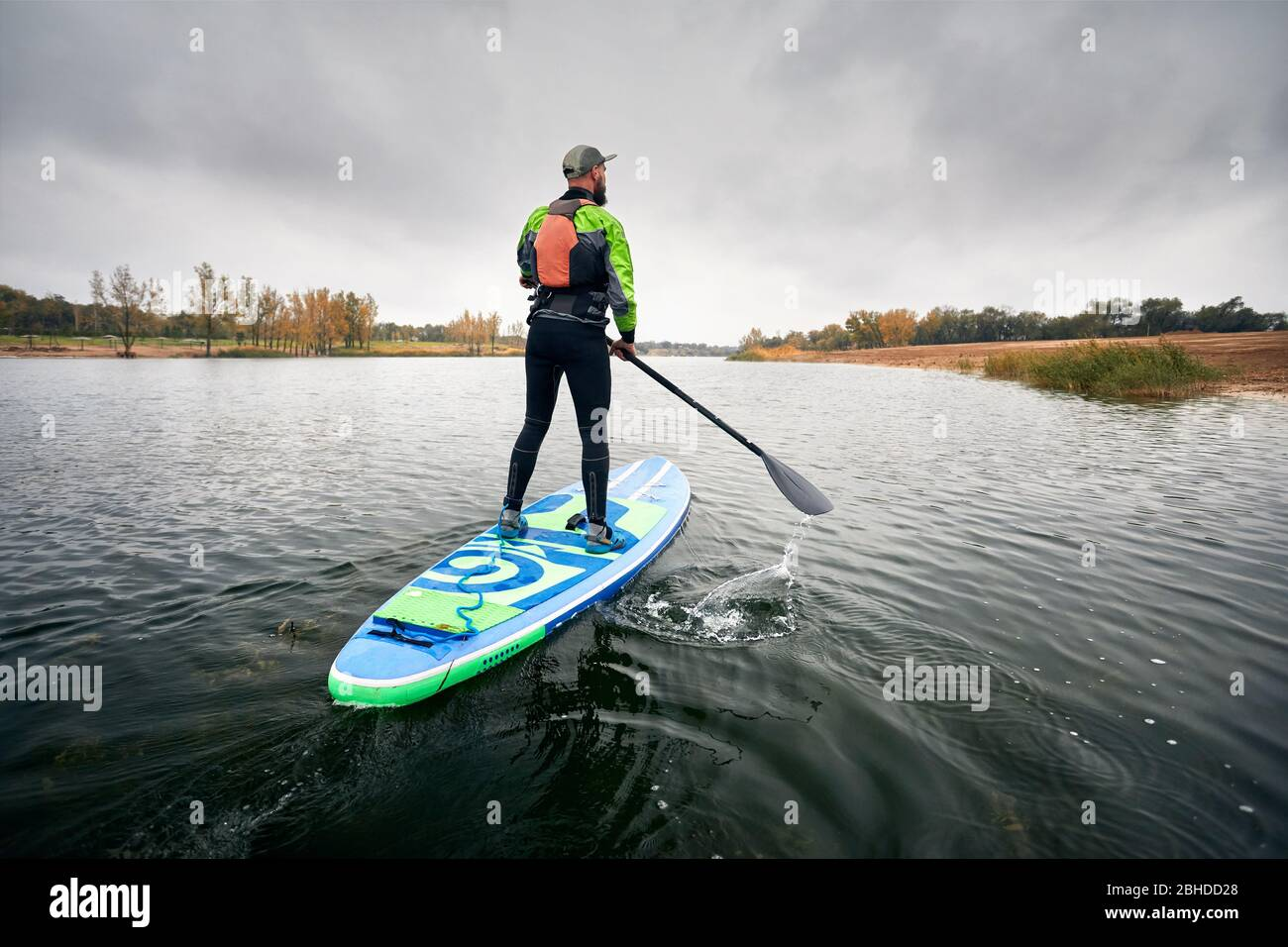 Athlete in wetsuit on paddleboard exploring the lake at cold weather against overcast sky Stock Photo