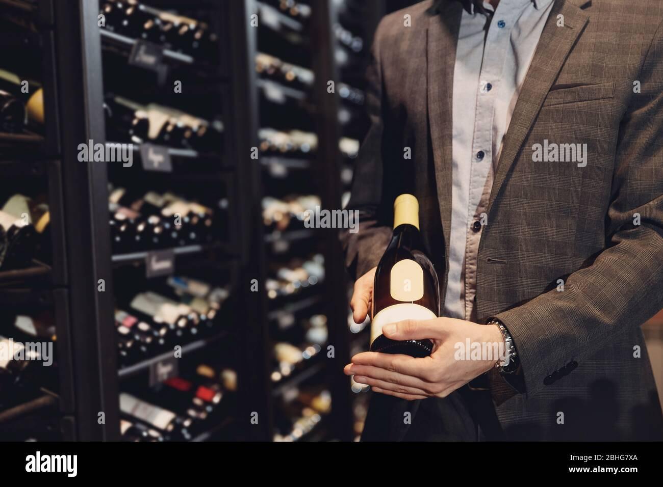 Bartender sommelier picks bottle of wine from rack in restaurant with exquisite drinks Stock Photo