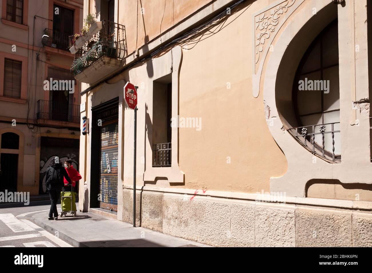 Dos personas con mascarillas charlan delante de tiendas cerradas por Cuarentena, 25 abril 2020, Gracia, Barcelona, España. Stock Photo