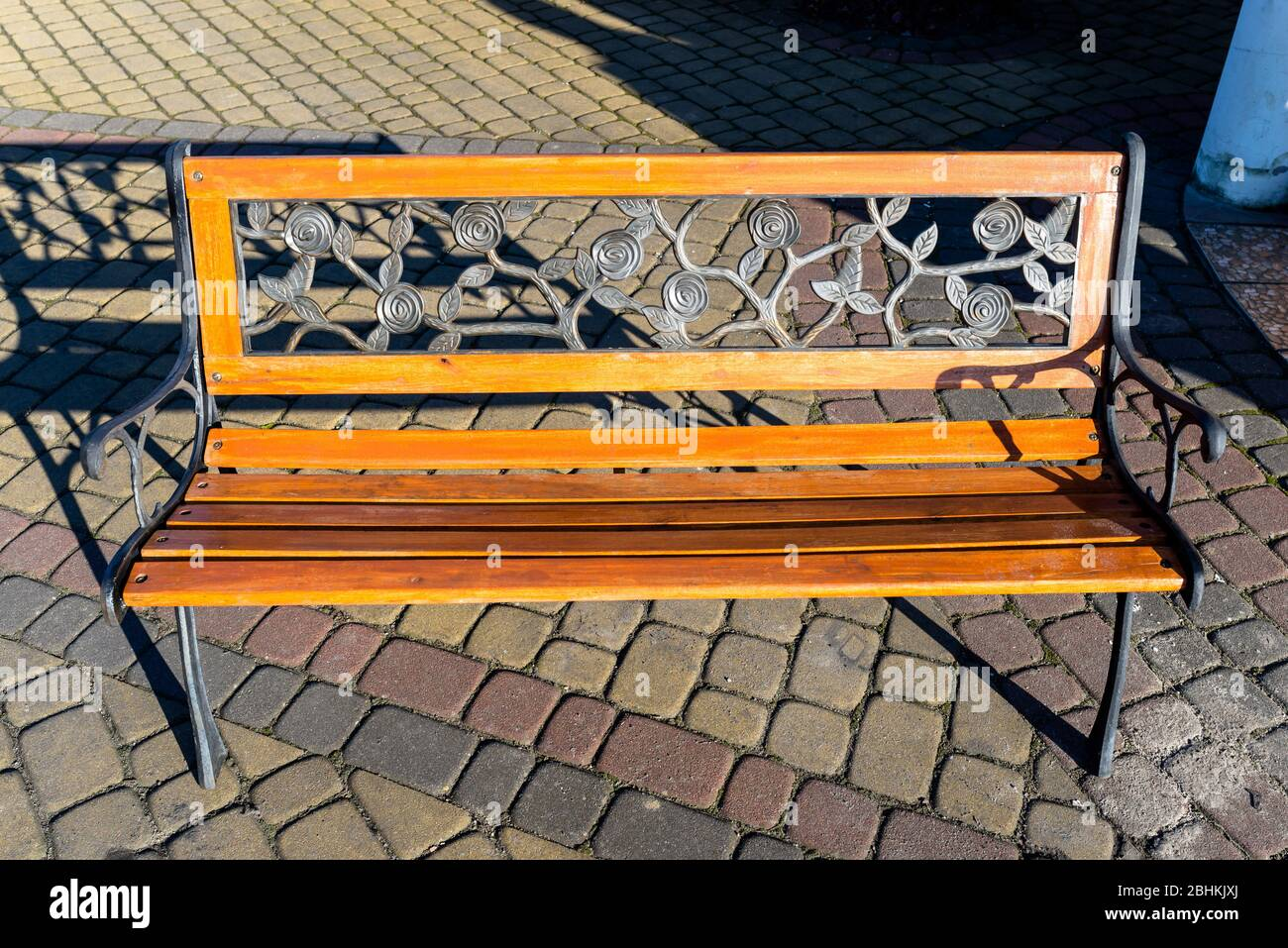 Picture of: A Decorative Bench Made By Hand From Wrought Metal In The Shape Of Leaves And A Wooden Seat Standing On A Paving Stone Stock Photo Alamy
