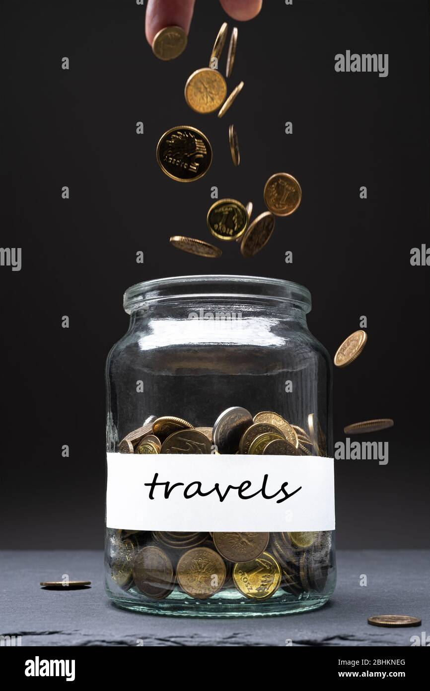 Coins in a jar with travels text on a white label. Caucasian man throwing money from above. Savings abstract concept. Copy space. Vertical orientation Stock Photo