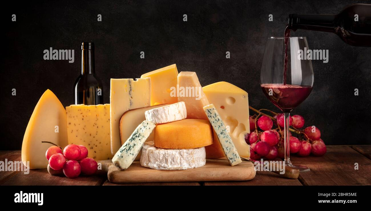 Cheese panorama, mvarious cheeses with grapes and pouring wine, a side view on a dark background with a place for text Stock Photo