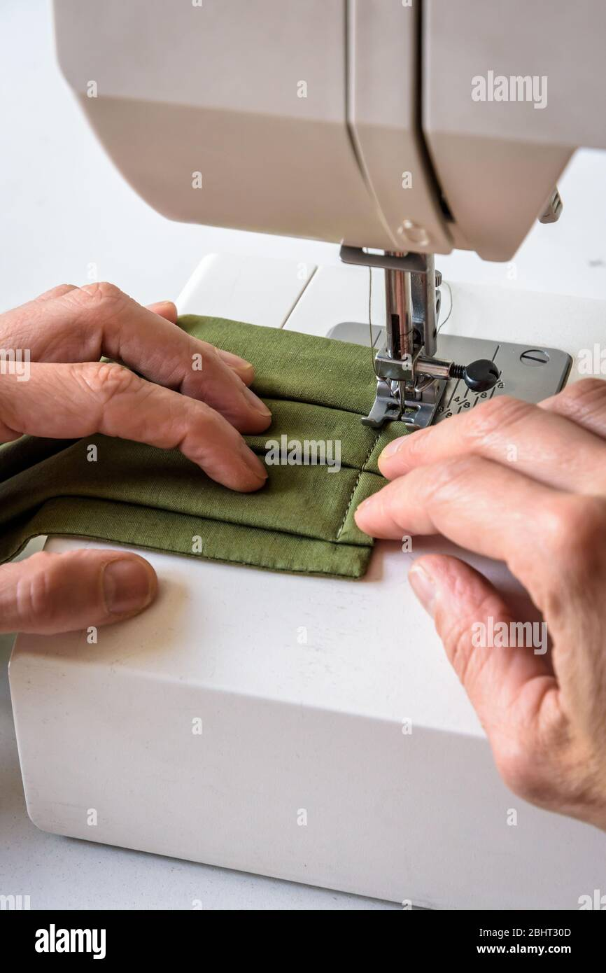 Close-up view on the hands of a woman sewing homemade reusable cloth face coverings in green cotton fabric on a sewing machine. Stock Photo