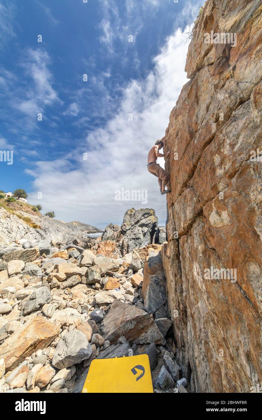 Male rock climber practicing bouldering without rope on a boulder area in front of the sea. A high boulder for people with tenacity and confidence Stock Photo