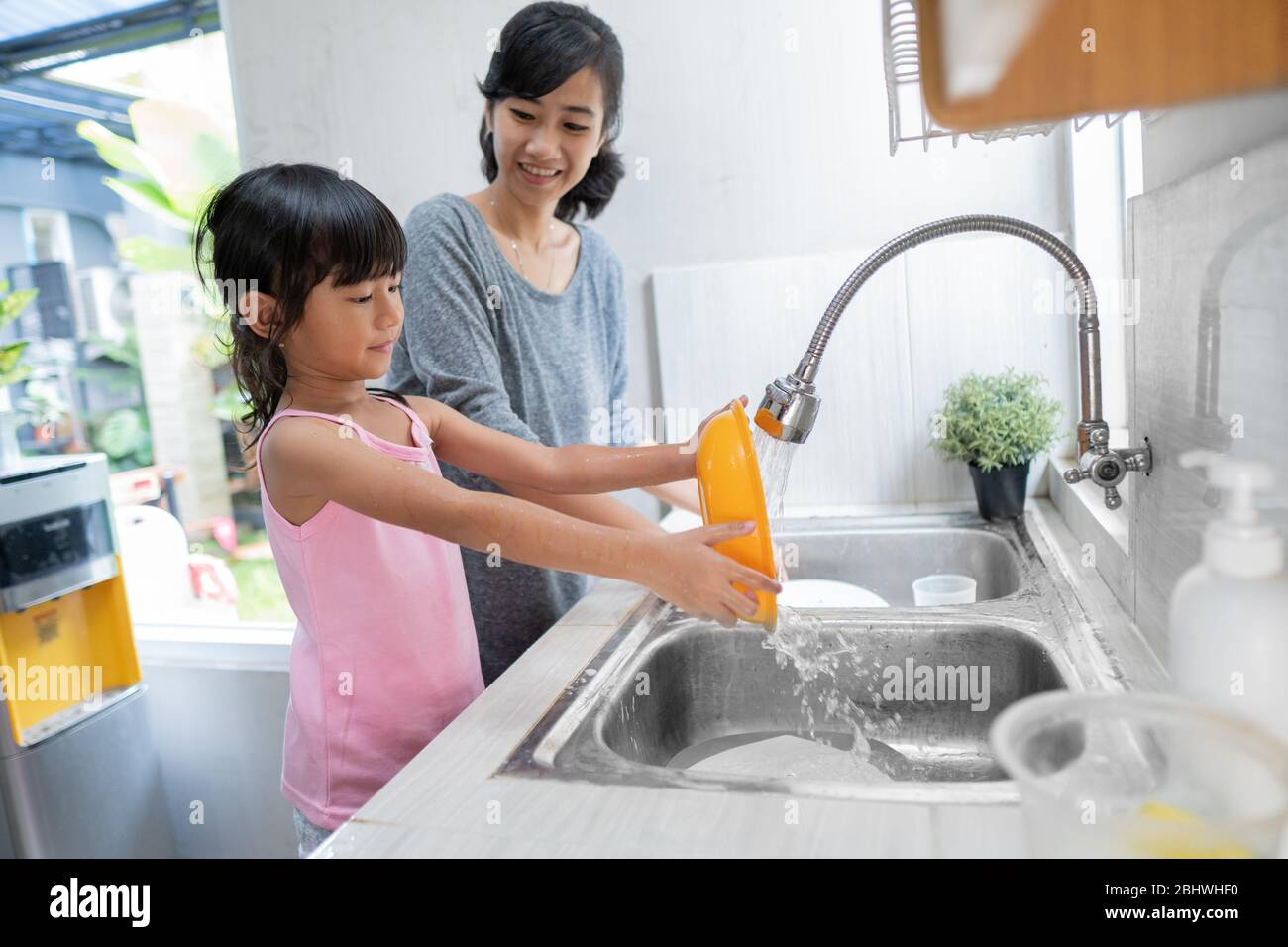 Helping hand. Cute little Girl Help Her Mother In Washing Dishes At Family Kitchen Stock Photo