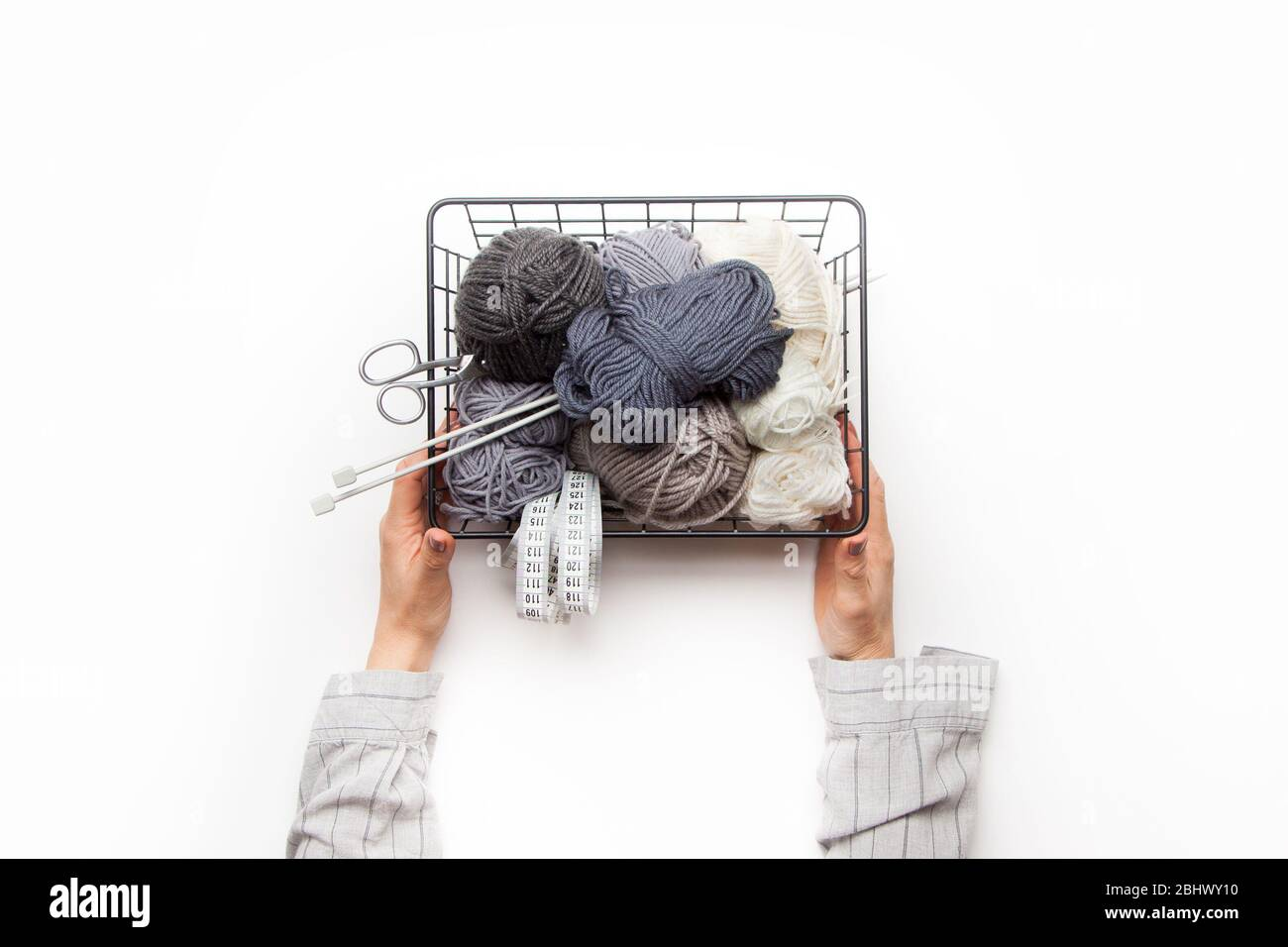 Female hands hold a black metal basket with yarn for knitting gray and white. Stock Photo