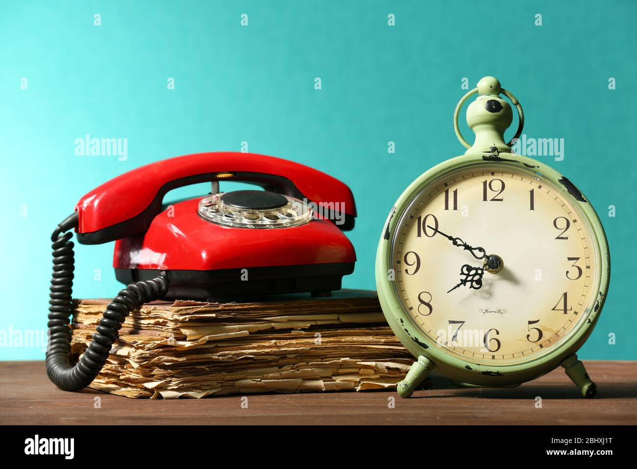 Retro Clock With Old Book And Telephone On Table On Green Background Stock Photo Alamy