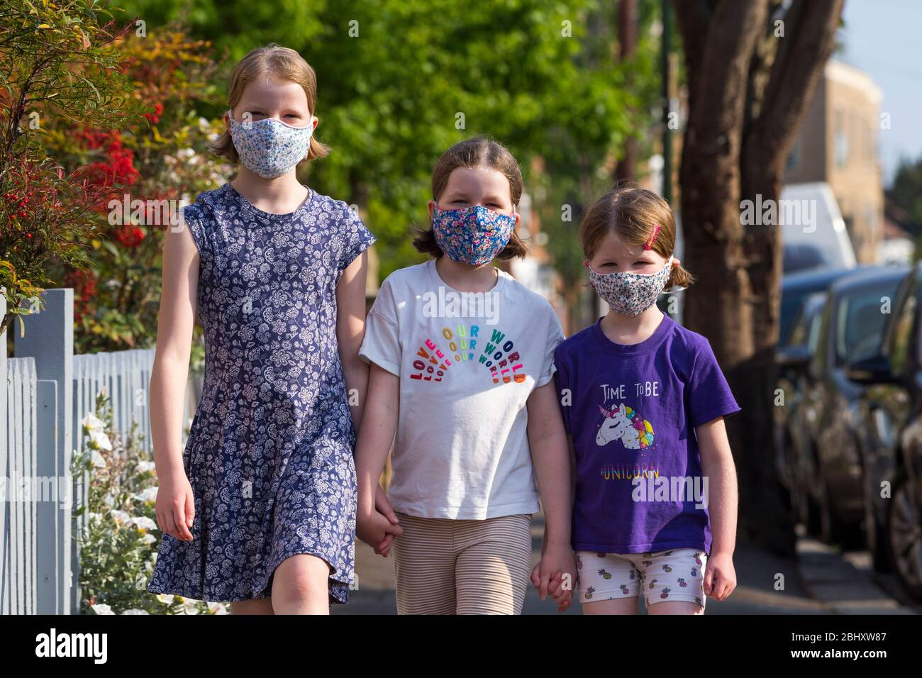 Three young sisters aged five years, 8 years & 10 years wearing masks that they've made at home with mum to wear during the COVID-19 / COVID 19 coronavirus pandemic of 2020; homemade face mask. UK. (118) Stock Photo