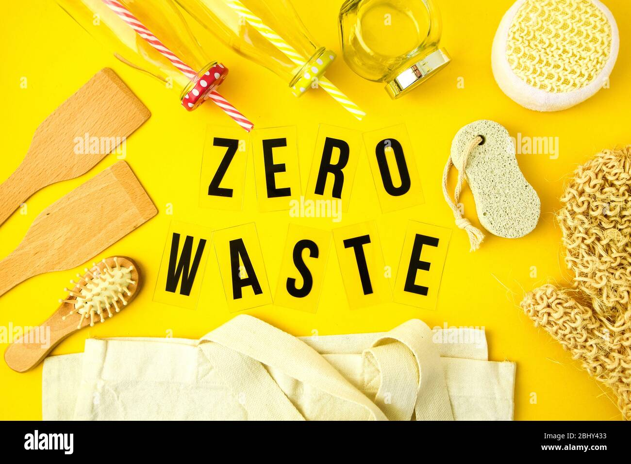 Zero waste concept. Textile eco bags, glass jars, wooden hair brush and washcloth and on yellow background with Zero Waste black text in center. Stock Photo