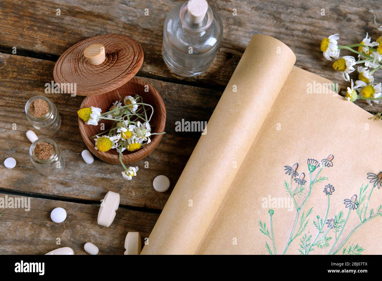 Old book with dry flowers in mortar on table close up Stock Photo