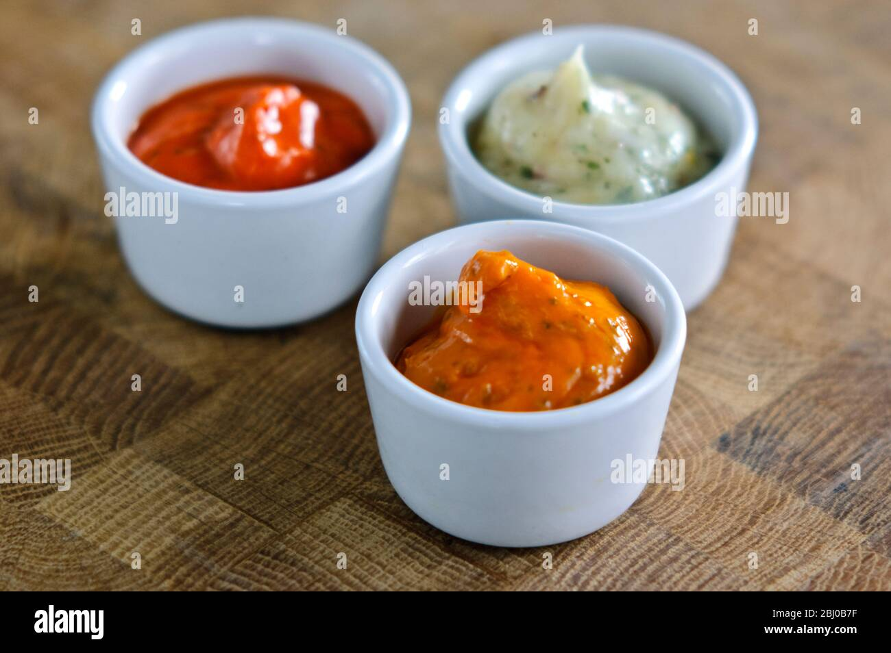 Small pots of commercial sauces used for glazing meaat before grilling. Also can be used as relish - Stock Photo