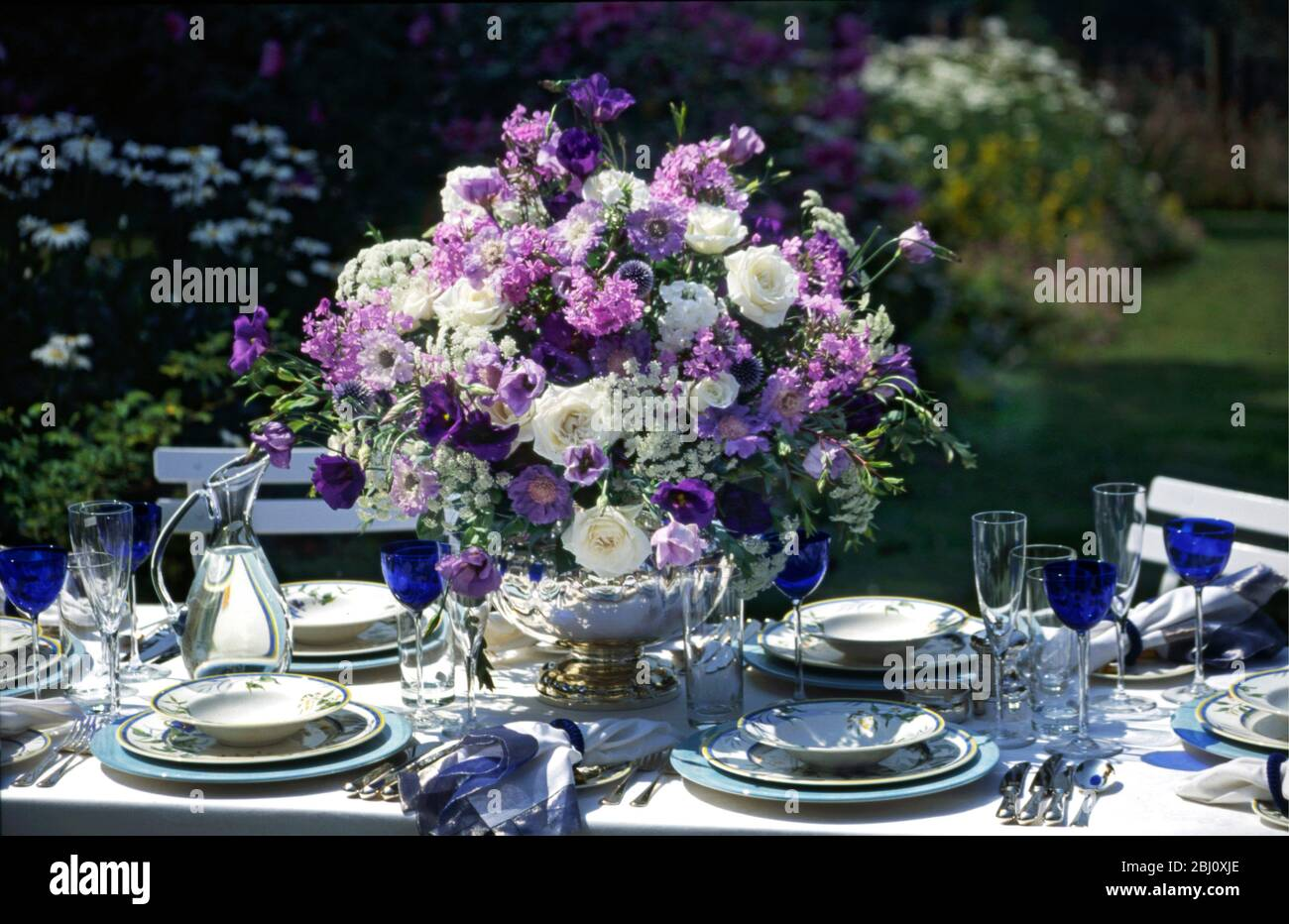 Amazing Blue And White Flower Arrangement In The Middle Of Formal Table Setting Arranged Outside In Summer Garden Stock Photo Alamy