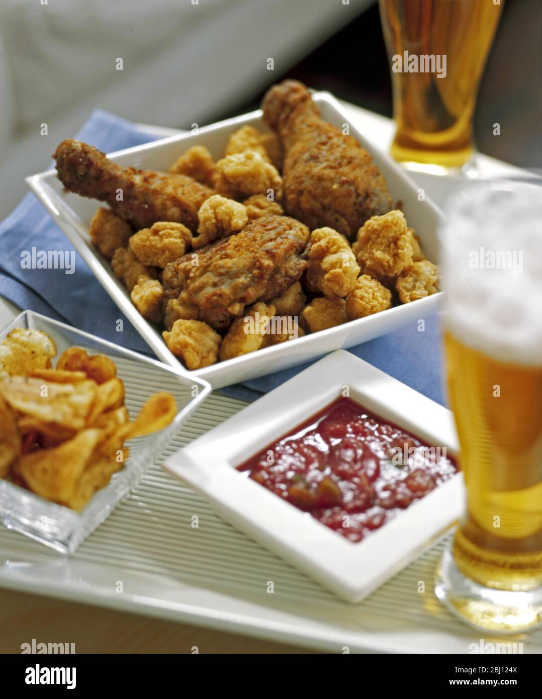 Casual Meal Of Fried Chicken Crisps Tomato Salsa And Beer Stock