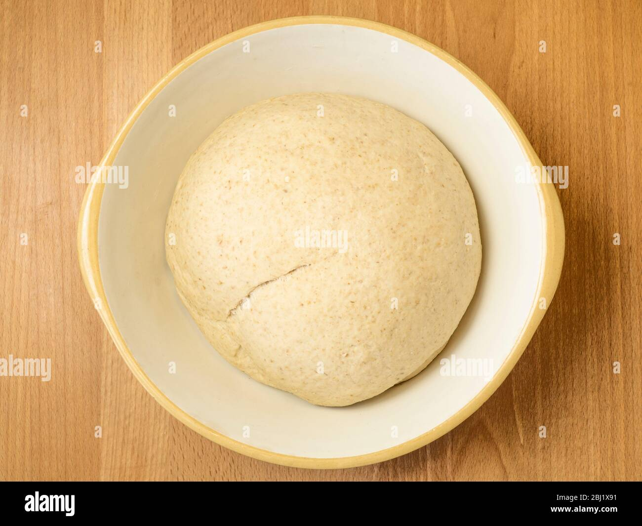 Oat bread dough doubled in size after the first prove before knocking back in a mixing bowl on a wooden kitchen table Stock Photo