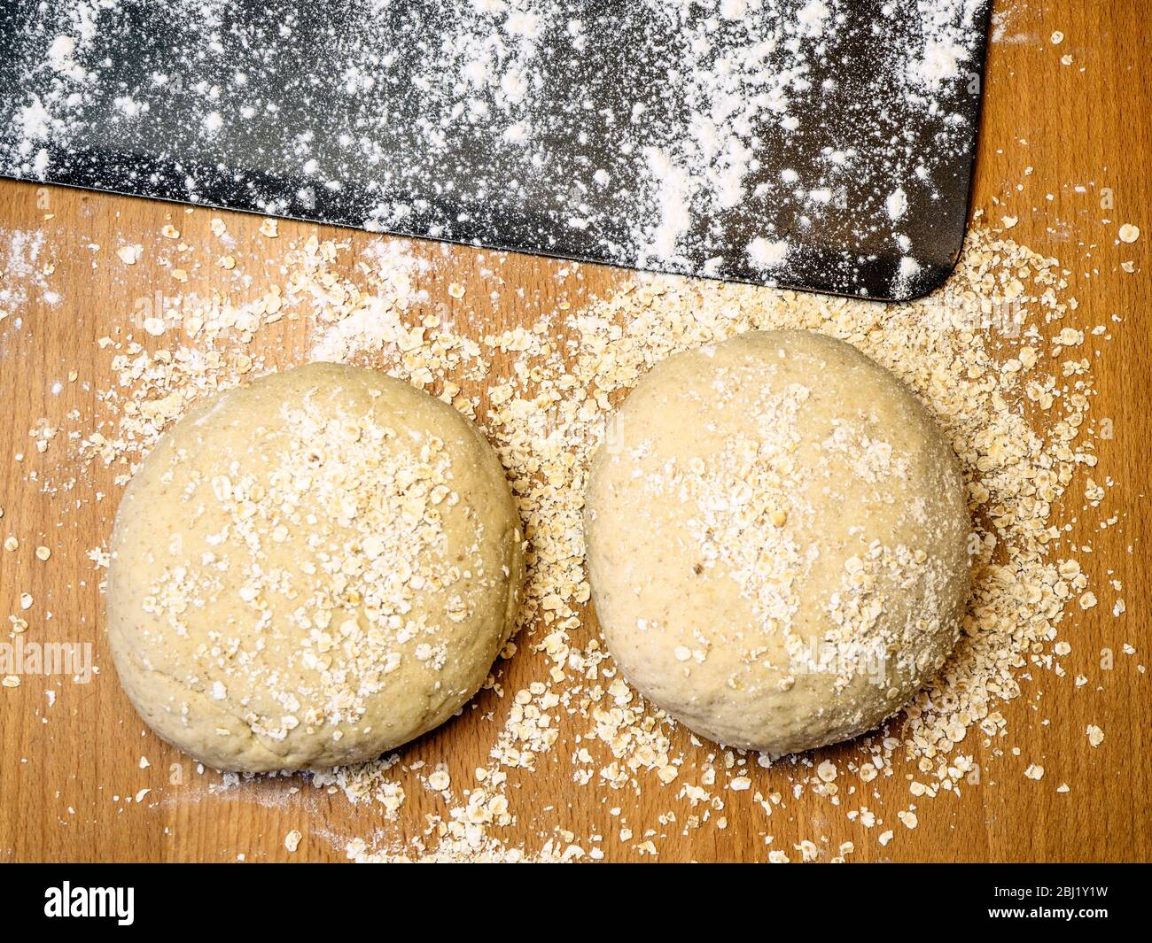 Two rounds of oat bread dough rolled in oats with a floured baking sheet on a kitchen table Stock Photo