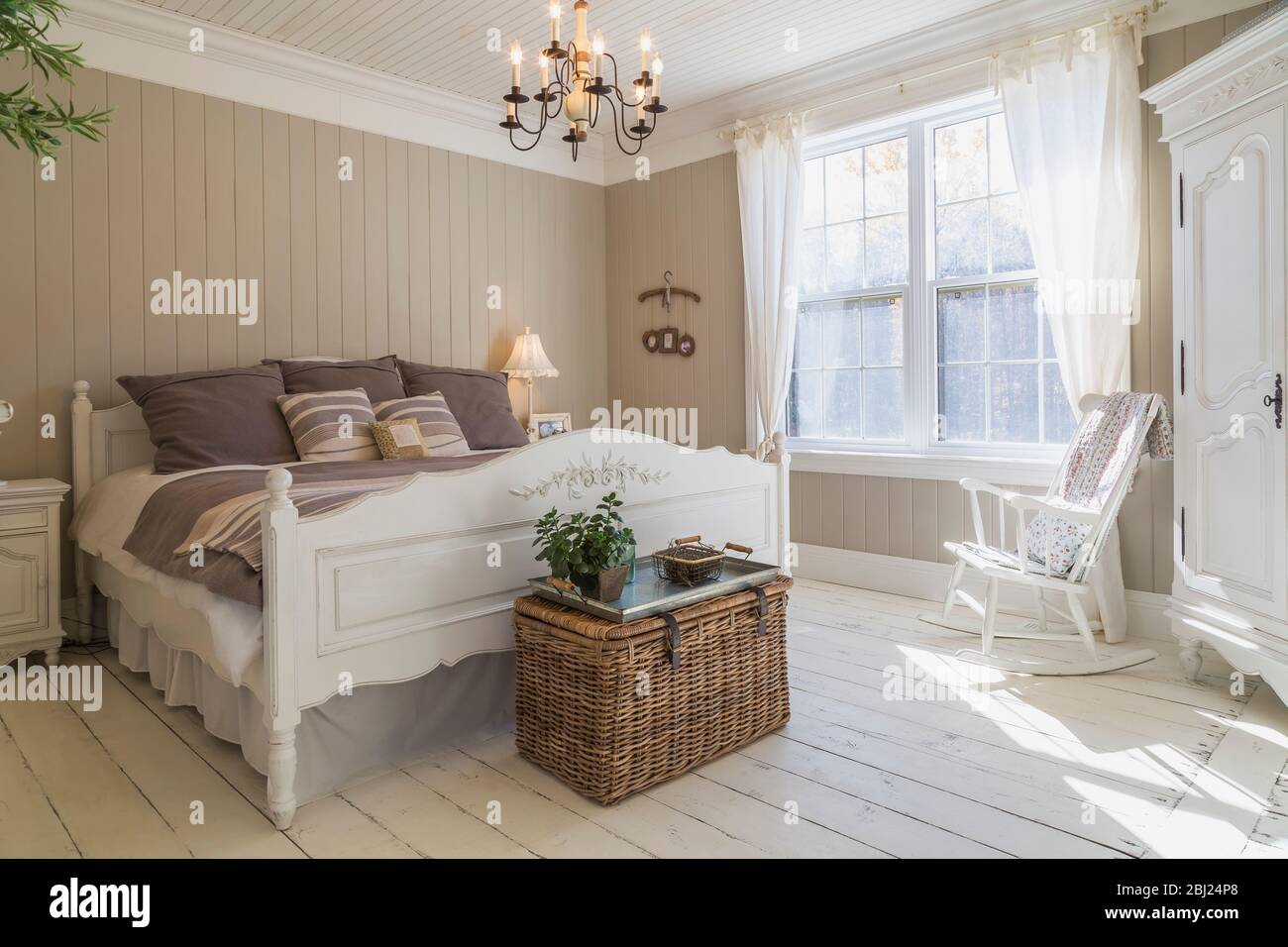 Bedroom With Double Bed Cream Painted Floorboards Brown Wood Panelled Wall White Furniture And Curtains Stock Photo Alamy