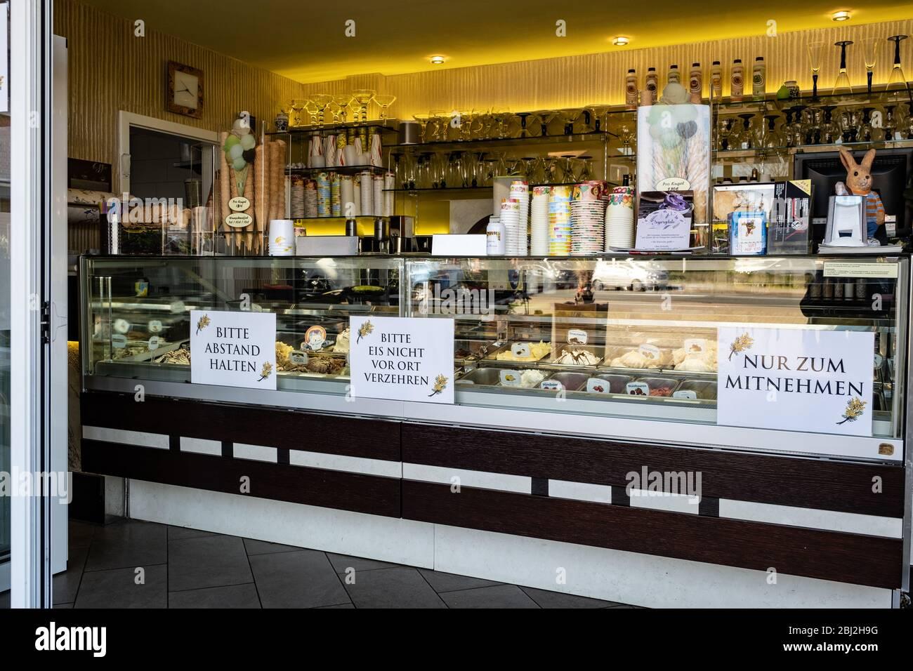 Ein Eisladen verkauft Eis zum Mitnehmen, es darf nicht vor Ort verzehrt werden. Schilder mit Hinweisen zum Abstandshalten am Tresen Stock Photo