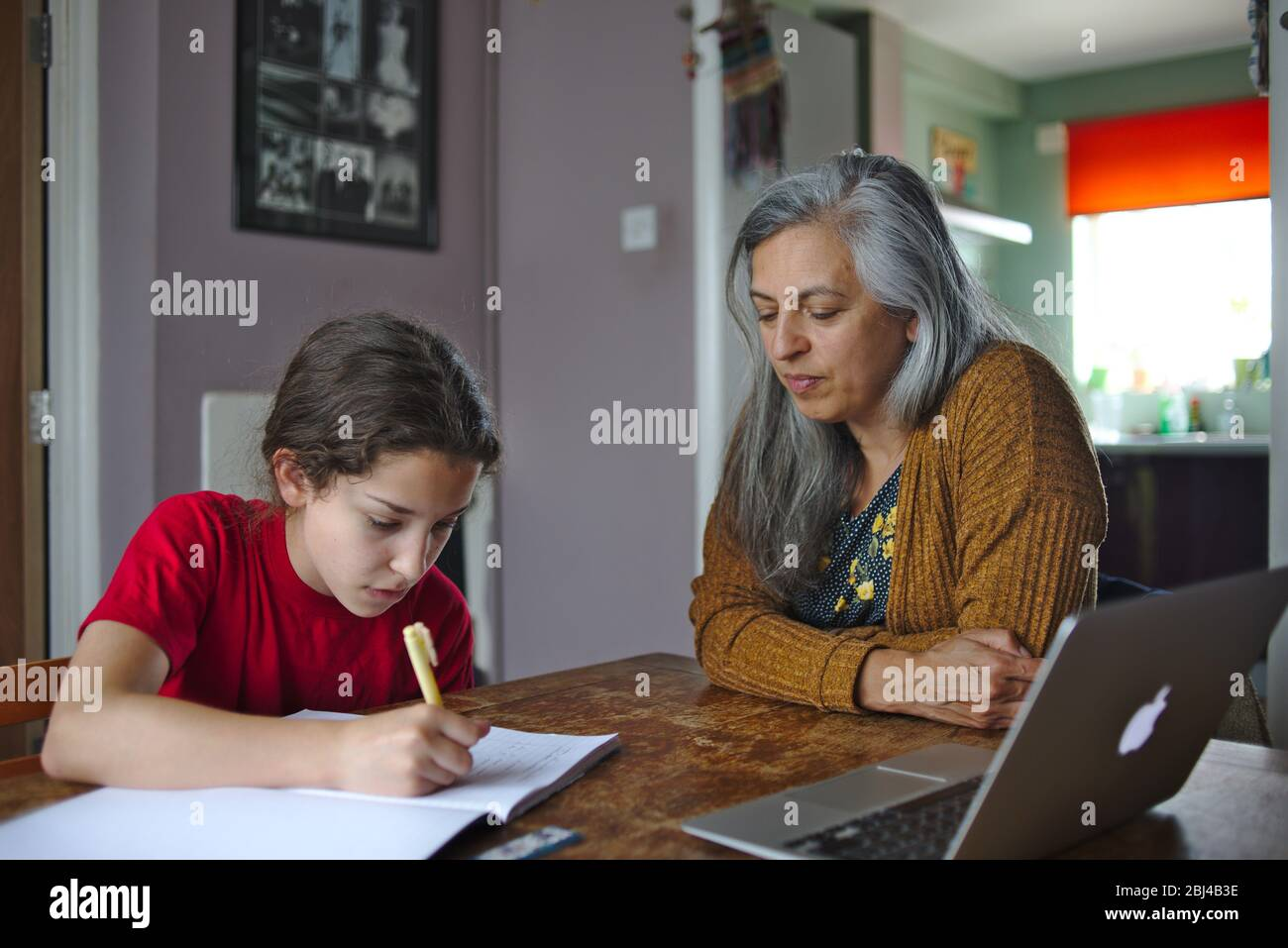 Parent helping child with school work at home during coronavirus lockdown. April 2020 UK Stock Photo