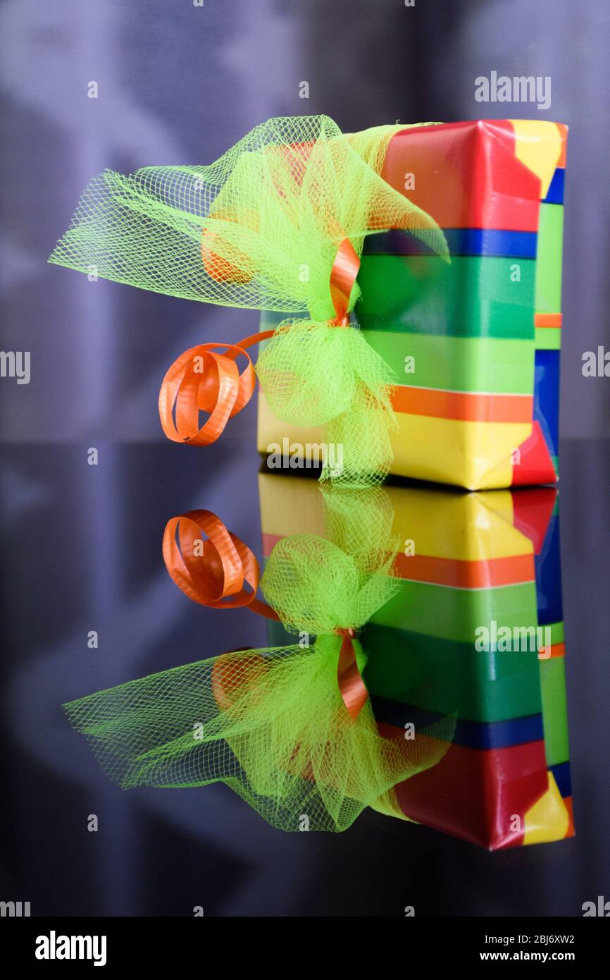 Bright and colourful gift box reflected in the glass table below Stock Photo