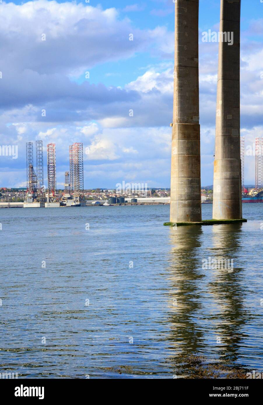 Oil rig drilling platforms  at Dundee Dockside with pier colums of Tay road bridge in foreground Stock Photo