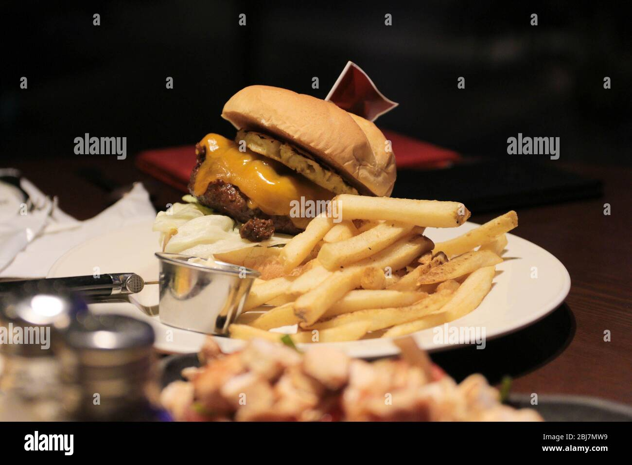 Classic burger with french fries and flag on top. Stock Photo