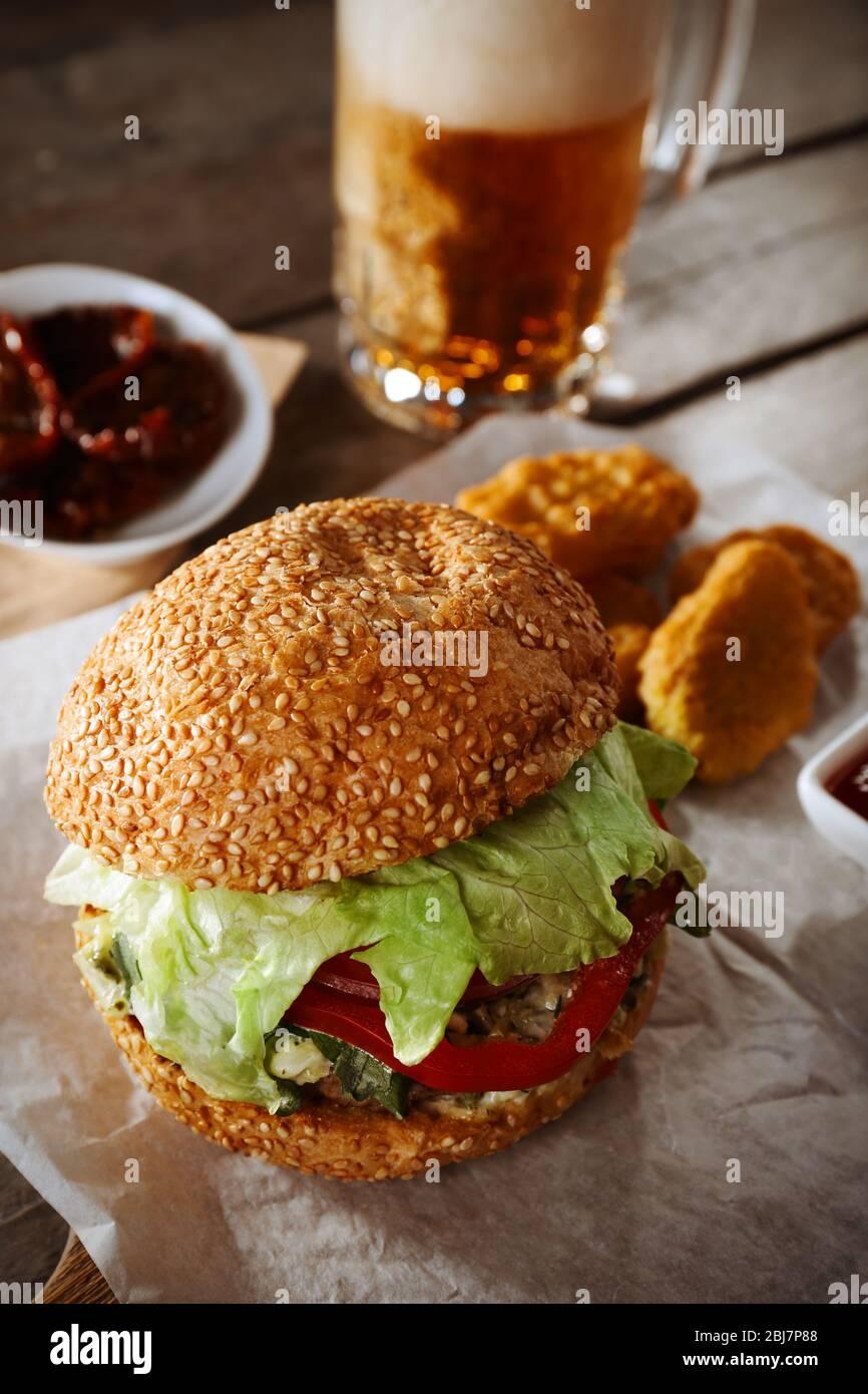 Big Tasty Hamburger With Snacks And Glass Mug Of Light Beer On Wooden Table Stock Photo Alamy