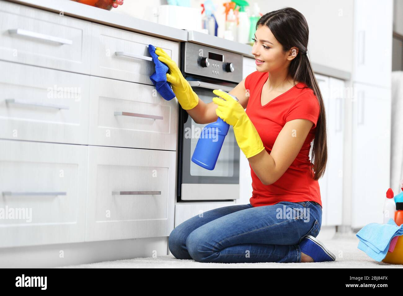 Beautiful woman in protective gloves cleaning kitchen cabinet Stock Photo