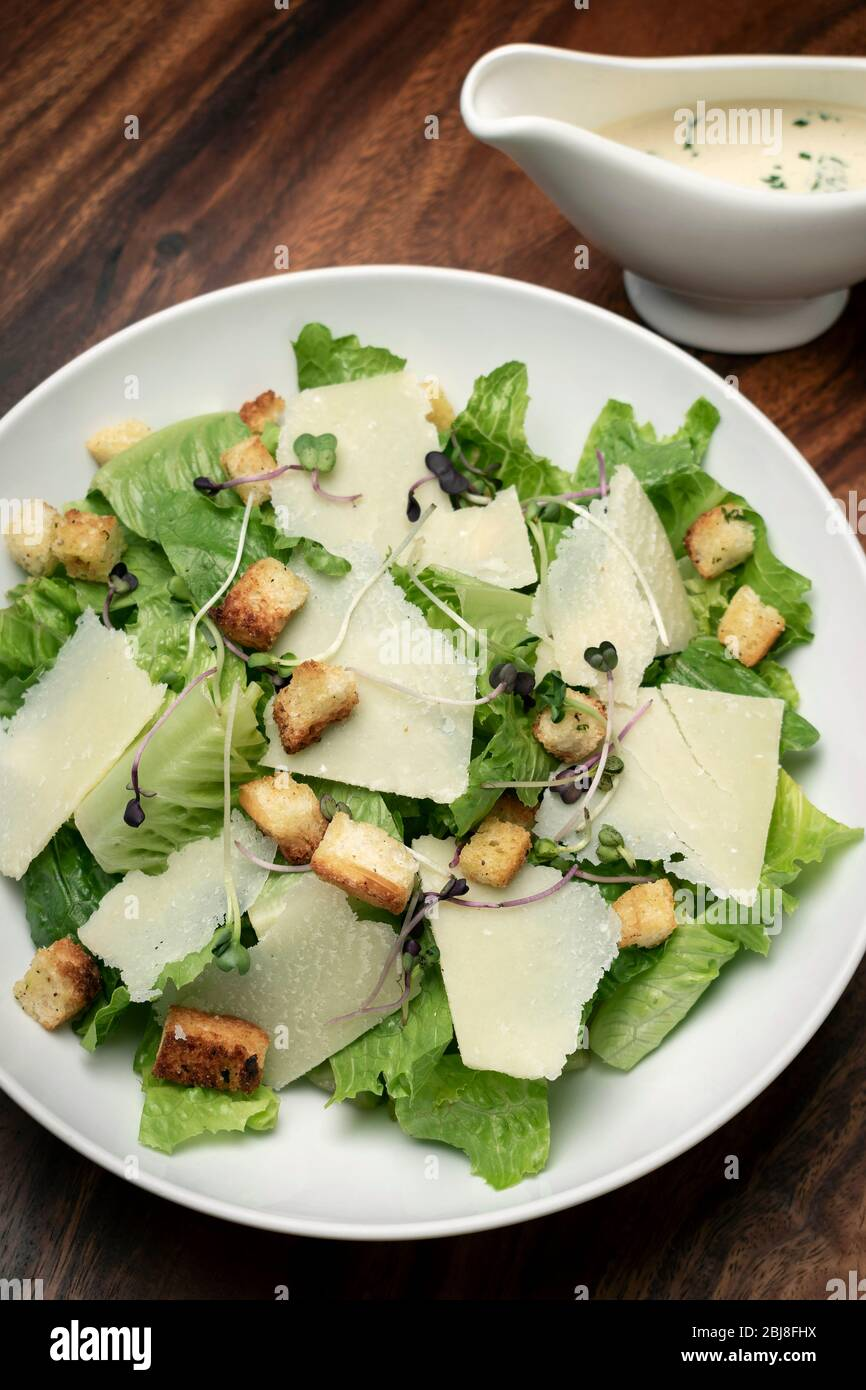 caesar salad with parmesan cheese and croutons on wood table Stock Photo
