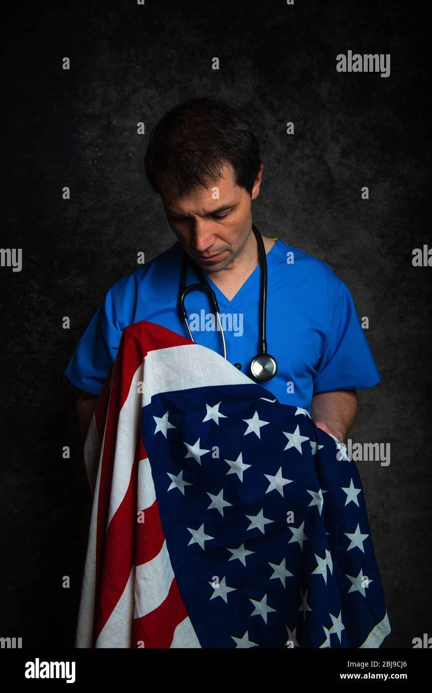 Sad/pensive male doctor in blue hospital scrubs with stethoscope, nursing the Stars & Stripes American flag close to his chest. Stock Photo
