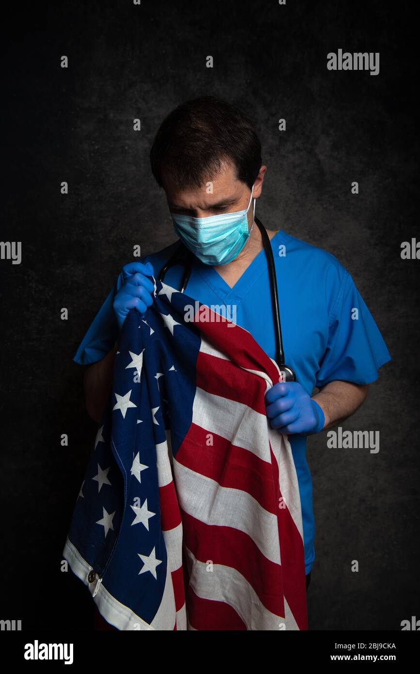 Sad/pensive, male doctor in blue hospital scrubs with face mask and stethoscope, nursing the Stars & Stripes American flag close to his chest. Stock Photo