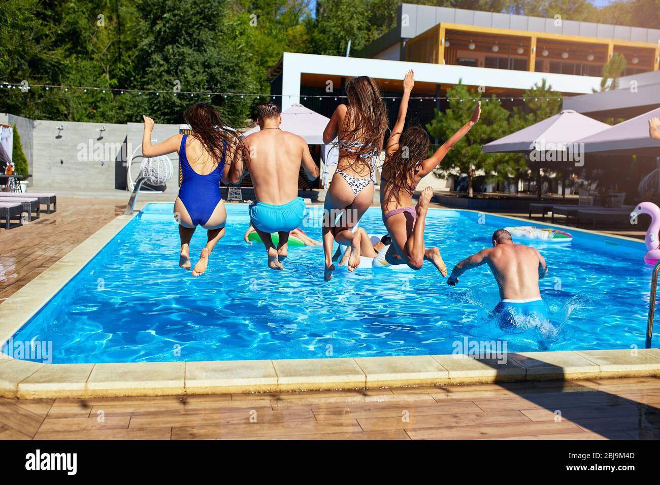 Happy friends jumping and splashing in swimming pool with inflatable floats in luxury resort. Young people in swimwear having party in private holiday Stock Photo