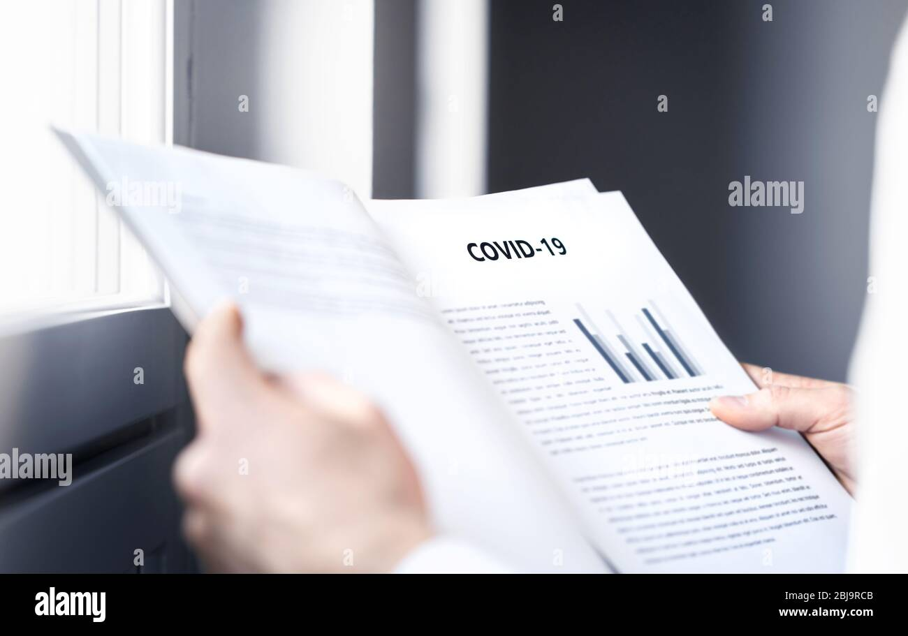 Coronavirus report about patient information or covid 19 impact on business finance market. Doctor reading virology laboratory research. Stock Photo
