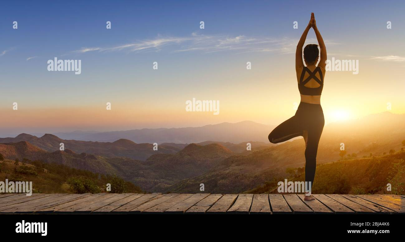 Young woman practicing yoga in the nature.female happiness. Pose balance body vital zen and meditation for workout nature mountain background in morni Stock Photo