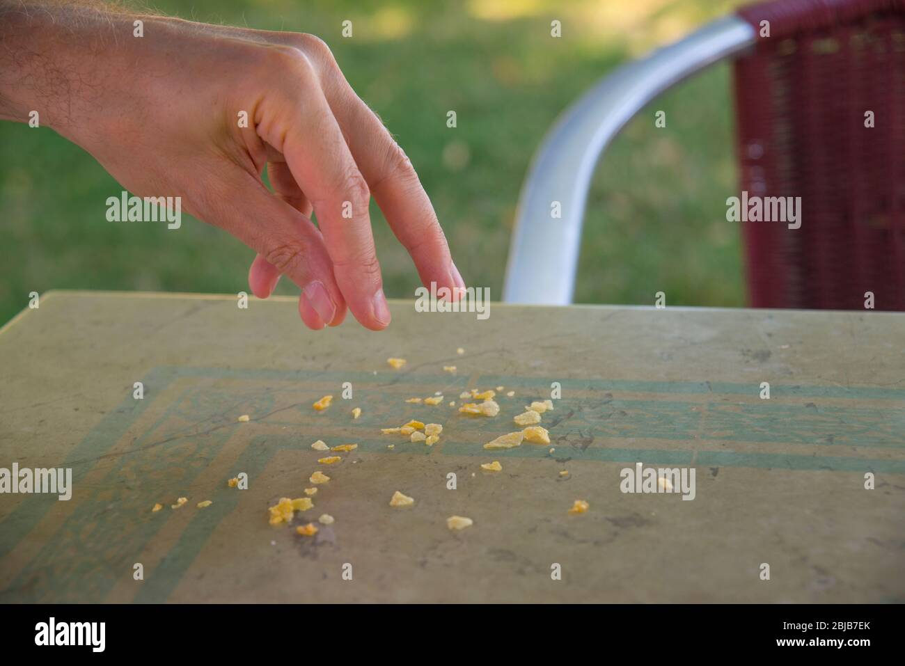 Feeding birds: man's hand dropping crumbles on the table of a terrace. Stock Photo
