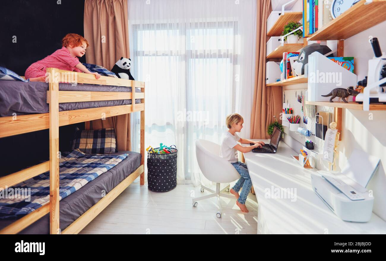 Two Boys Brothers In Kids Room With Bunk Bed And Wall Shelves Stock Photo Alamy
