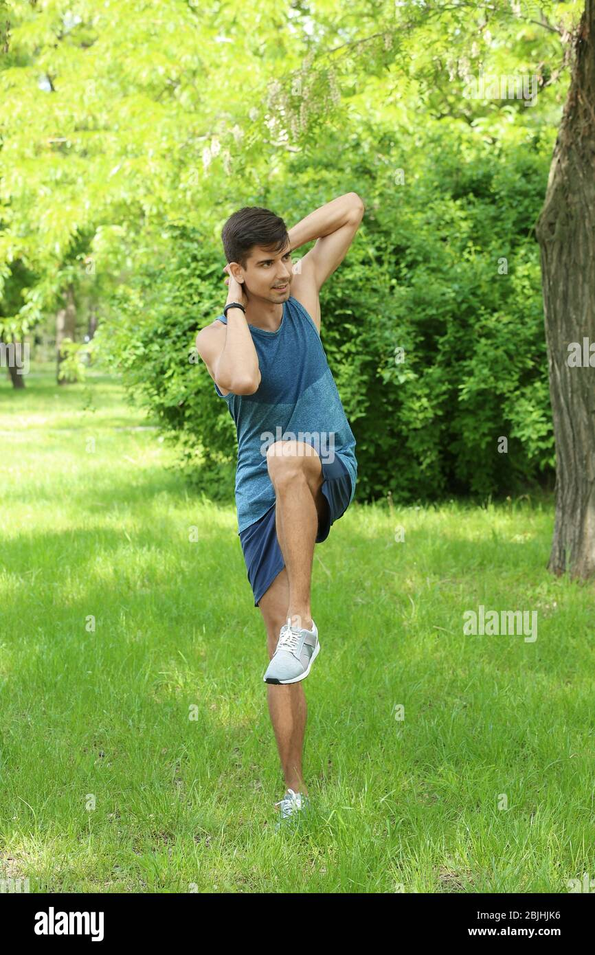 Athletic Young Man Doing Bicycle Crunch Exercise While Standing On Grass In Green Spring Park Stock Photo Alamy