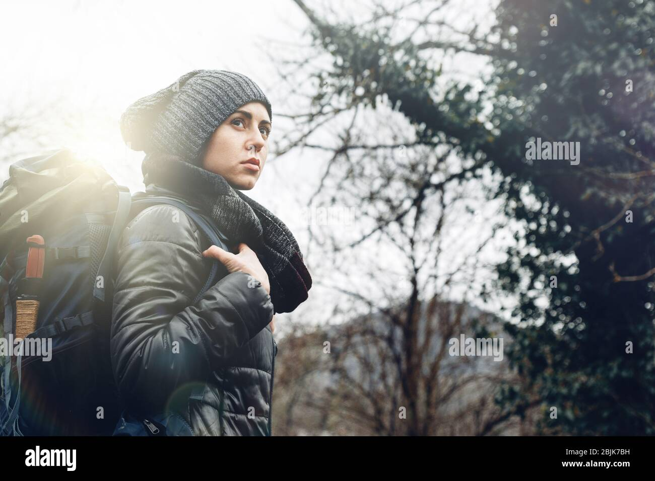 Young woman with backpack in forest. Concept Travel Tourism Adventure Hike and People Stock Photo
