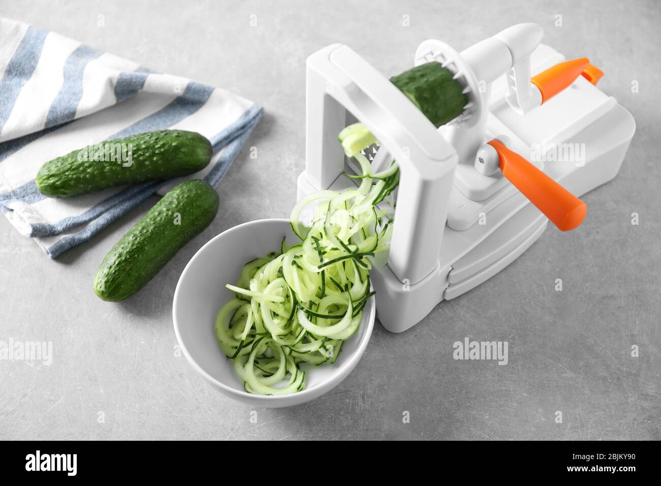 Spiral vegetable slicer with cucumber spaghetti on table Stock Photo