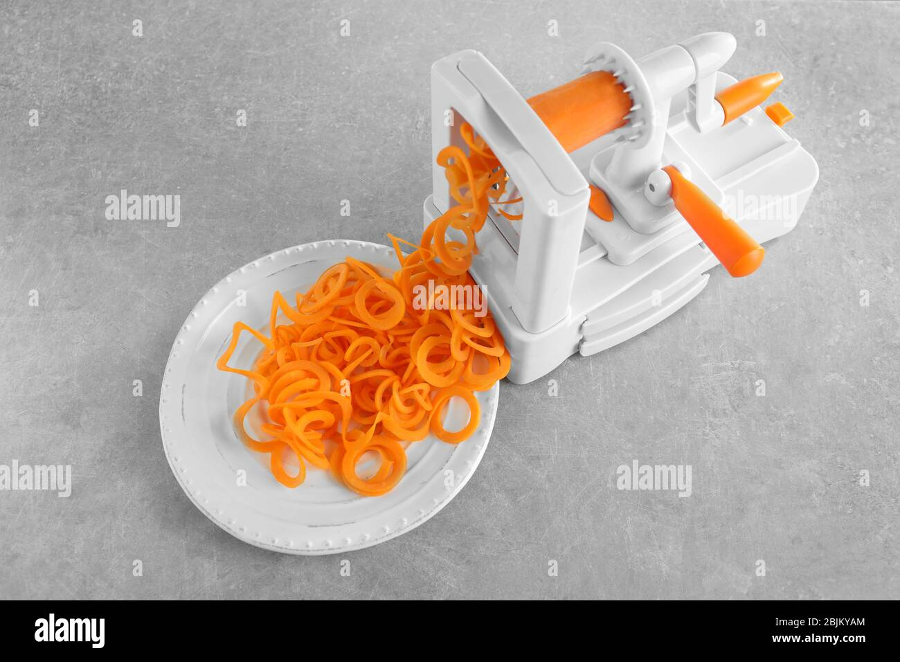Spiral vegetable slicer with carrot spaghetti on table Stock Photo