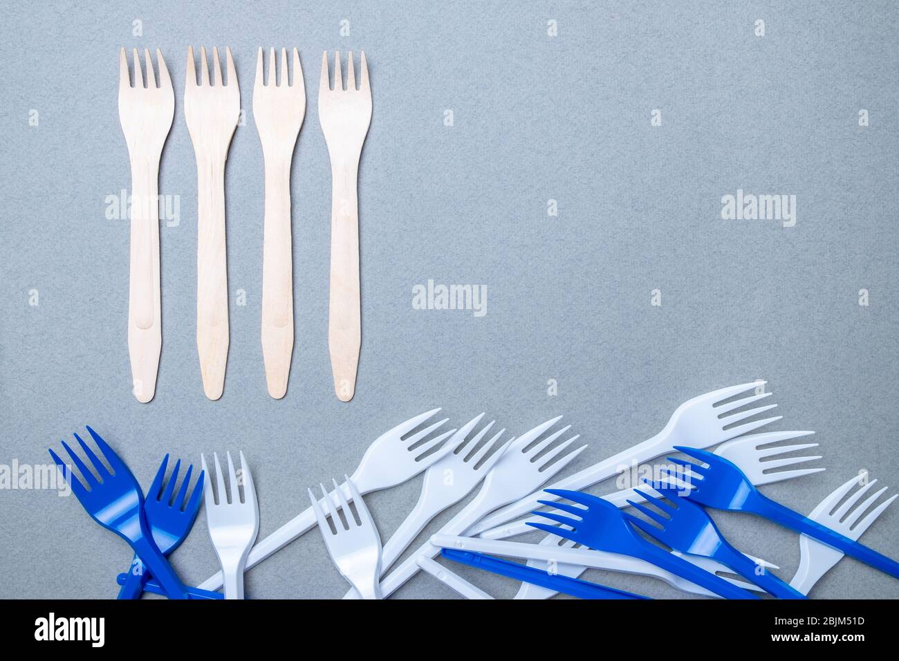 Forks made of wood and plastic on a gray background. Flat lay. Copy space. The concept of environmental pollution by difficult decomposable waste. Stock Photo