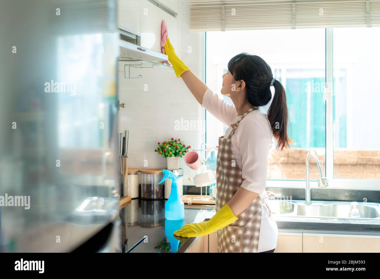 Asian woman wearing rubber protective gloves cleaning kitchen cupboards in her home during Staying at home using free time about their daily housekeep Stock Photo