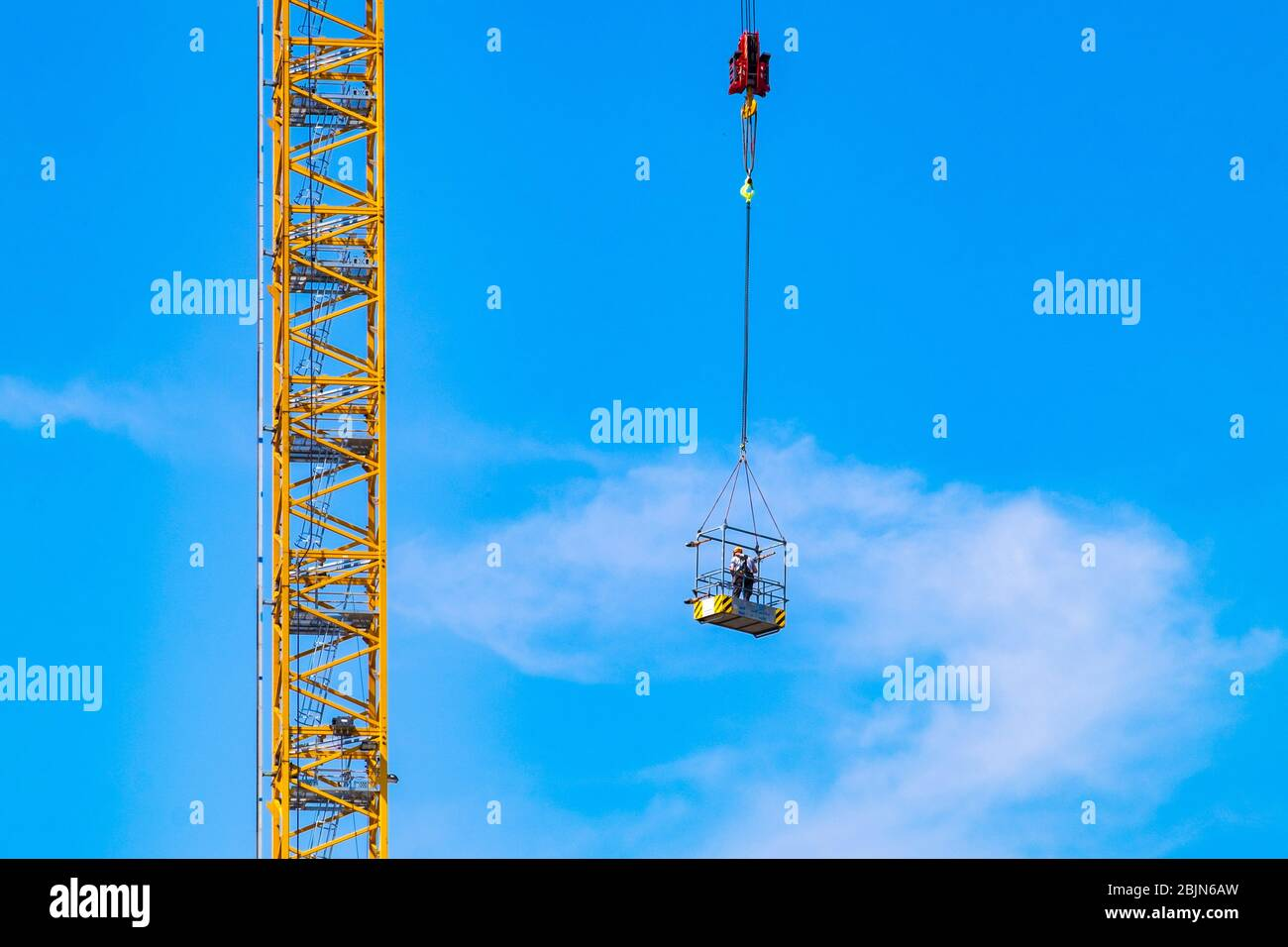 Construction worker hoisted up at a construction site at Strijp-S, Eindhoven, The Netherlands. Stock Photo