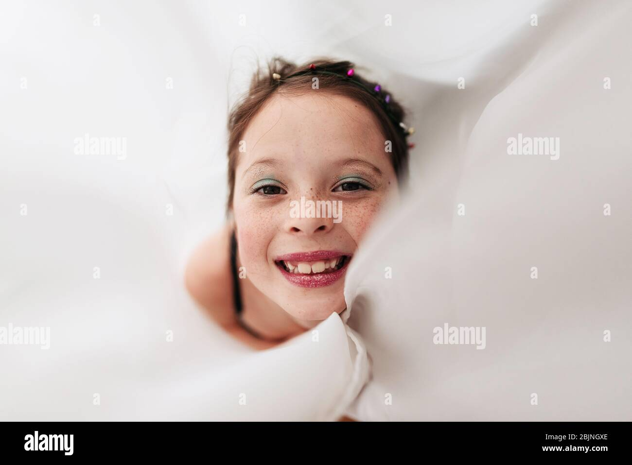 Portrait of a young girl wearing make-up wrapped in a curtain Stock Photo