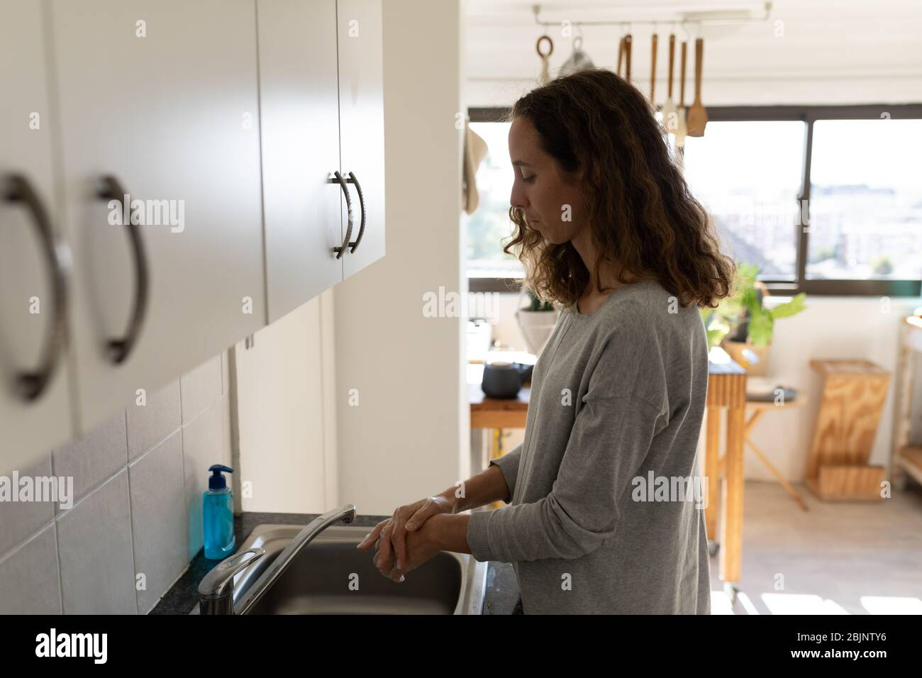 Caucasian woman spending time at home self isolating and social distancing in quarantine lockdown du Stock Photo