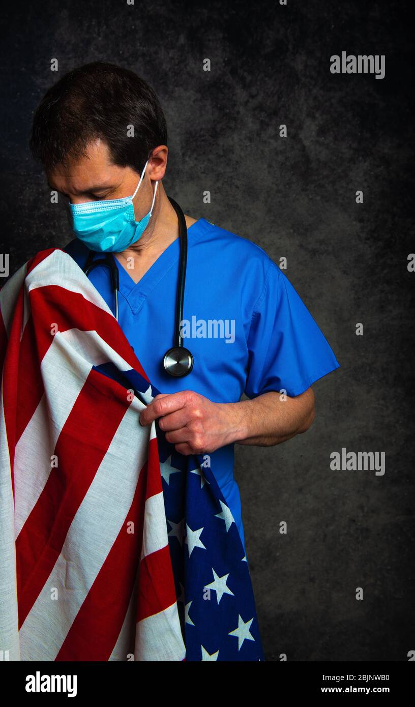 Sad/pensive male doctor in blue hospital scrubs with face mask and stethoscope, nursing the Stars & Stripes American flag close to his chest. Stock Photo